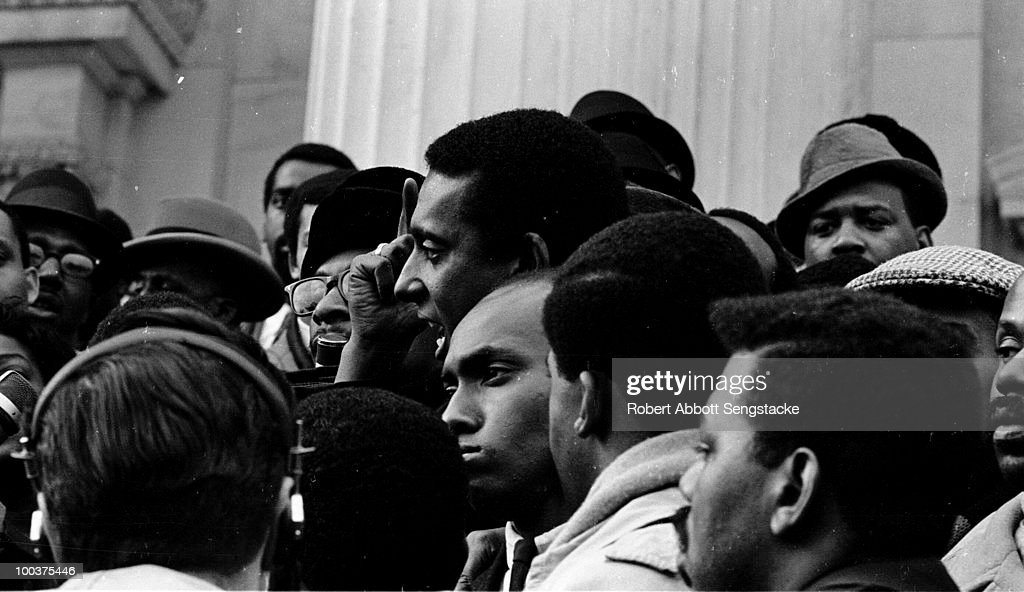 Stokely Carmichael (1941 - 1998) interviewed by the media while standing with supporters of US Congressman Adam Clayton Powell, Jr., who have gathered in protest of Powell's having been stripped of the chairmanship of the Education and Labor Committee, January 1967.