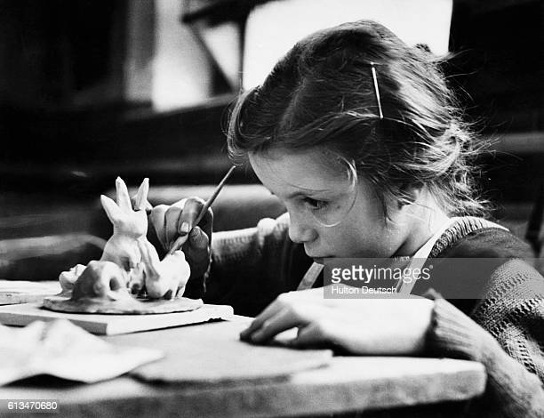 A StokeonTrent schoolgirl sculpts a group of rabbits from clay during pottery clas