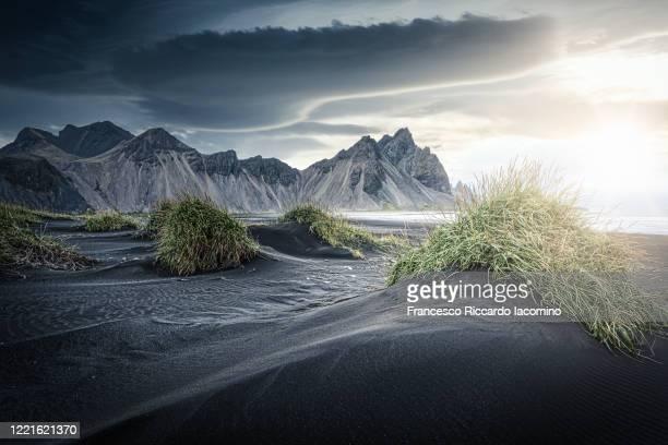 stokksnes, hofn, east iceland, iceland. vestrahorn mountain and the black sand dunes in a moody dramatic sunset. - francesco riccardo iacomino iceland foto e immagini stock