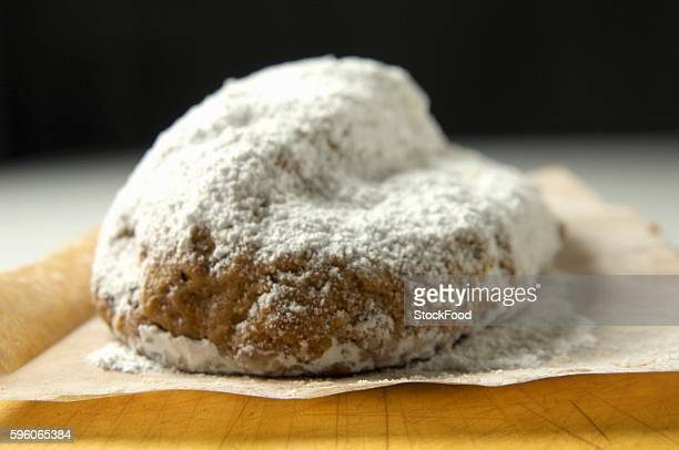 Stollen with icing sugar on baking paper