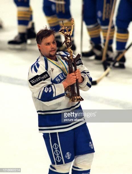 Stolz trägt der finnische Mannschaftskapitän Timo Jutila nach dem WeltmeisterschaftsFinale am 070595 in Stockholm den WMPokal über das Eis Durch...