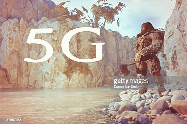 Stone age man with furs and weapons standing in river gorge looking at glowing new 5G technology sign