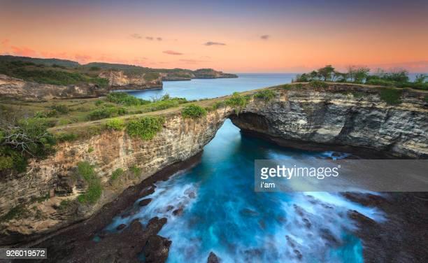 Stone arch over the sea. Broken beach, Uug beach, Nusa Penida, Indonesia. soft tones and warm sunset.