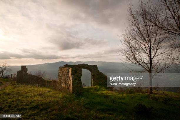 stone arched entrance of a medieval ruin in the countryside near volterra, tuscany, italy - monastery stock pictures, royalty-free photos & images