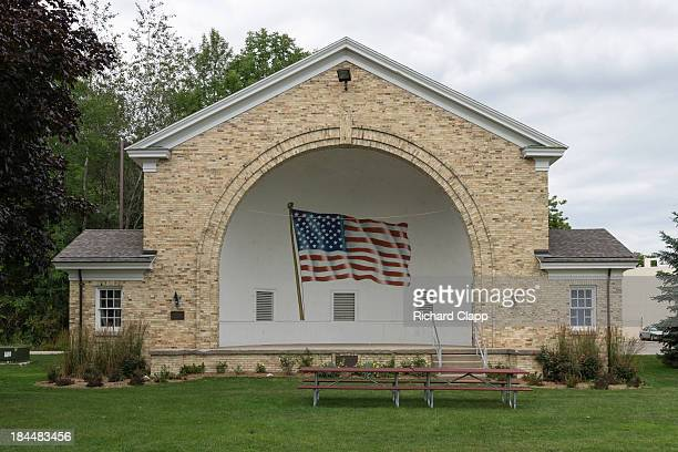Stone band shell in a park in Sheboygan, WI. Band shell has a large American Flag painted on back. A patriotic scene. Interesting architecture.