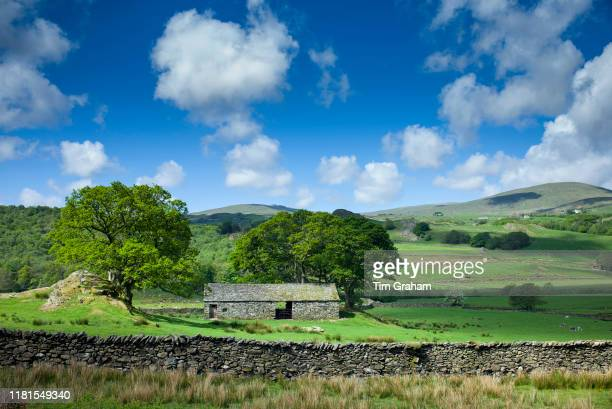 Stone barn and puffy clouds in blue sky near the River Duddon with Whitefell in the background in the Lake District Cumbria England