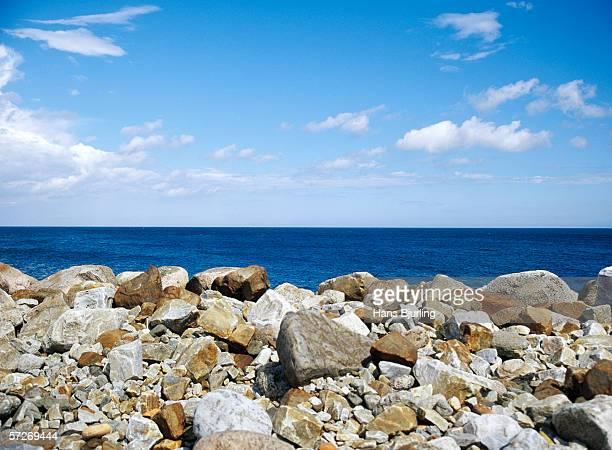A stone beach and clear blue sea.