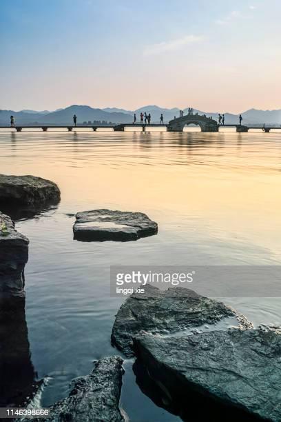 stone bridge and sunset scenery on west lake, hangzhou, china - west lake hangzhou stock pictures, royalty-free photos & images