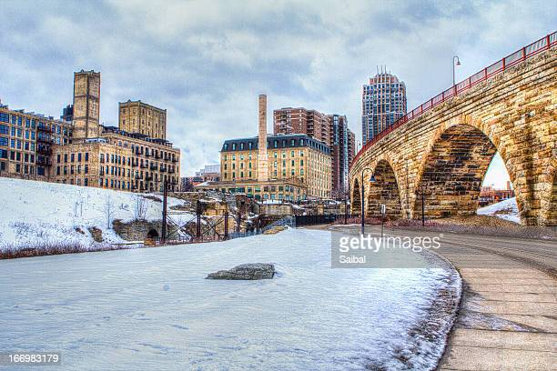 stone bridge connecting to city - minneapolis stock photos and pictures