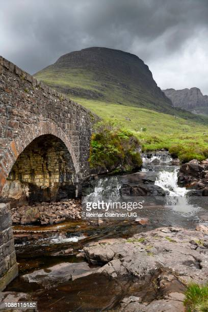 stone bridge of bealach na ba road mountain pass over russel burn river and sgurr a chaorachain peak in scottish highlands scotland uk - wester ross stock pictures, royalty-free photos & images