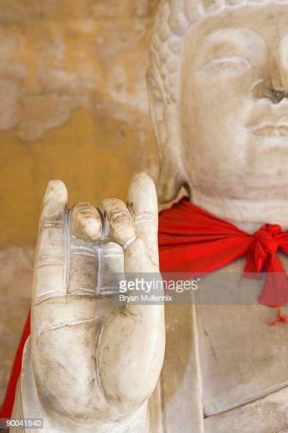 Stone Buddha with red cape at Tibetan Buddhist monument