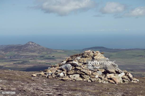 A stone cairn on a hilltop close to the coast