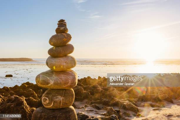 stone cairn pyramid on the beach during sunset - 石塚 ストックフォトと画像