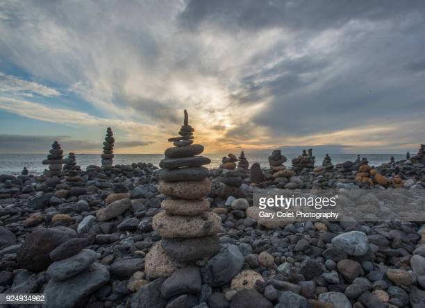 stone cairns on beach - gary colet stock pictures, royalty-free photos & images