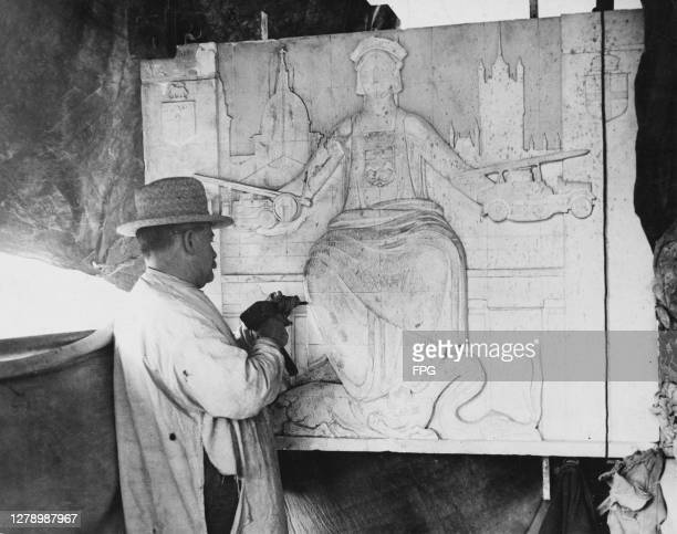 Stone carver at work on an allegorical stone relief depicting a goddess with a fire engine held in each of her outstretched hands, with the dome of...