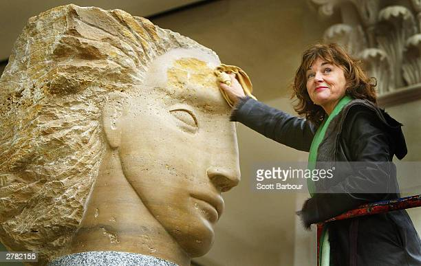 Stone carver Emily Young polishes one of her new works which was unveiled at St Paul's Churchyard on December 4 2003 in London England The five giant...