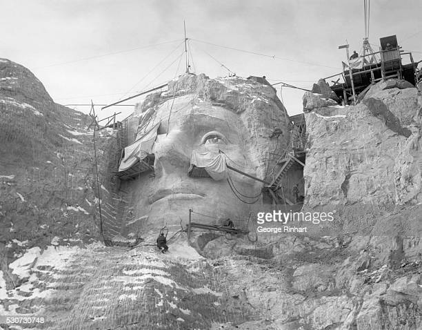 Stone carvers on scaffolding and hoists carve the face of Thomas Jefferson into Mount Rushmore