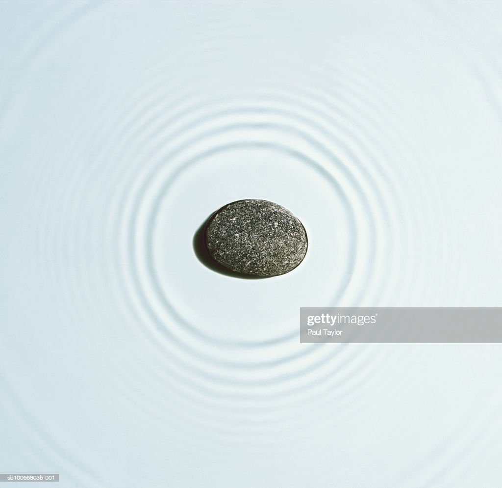 Stone causing ripples on water, close-up : Stock Photo