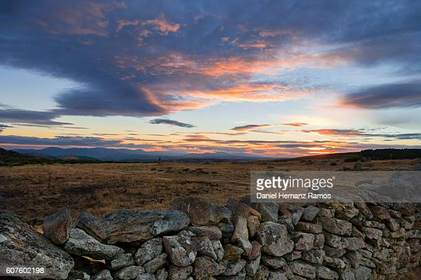 Stone fence in foreground and yellow meadow in background in summer. Sierra de Guadarrama. Madrid, Spain. Mountains at sunset with clouds