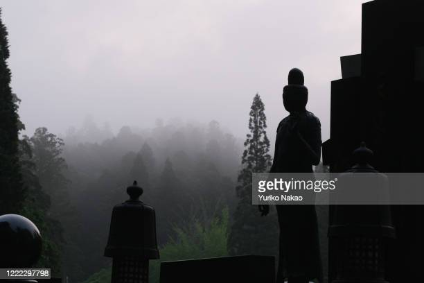A stone grave and a buddhist statue stand in Okunoin cemetery where the mausoleum of Kobo Daishi also known as Kukai the founder of Shingon Buddhism...