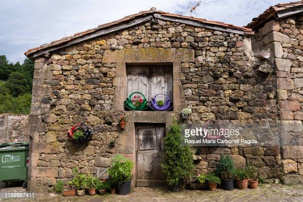 Stone house doorway beautifully decorated with flower pots.
