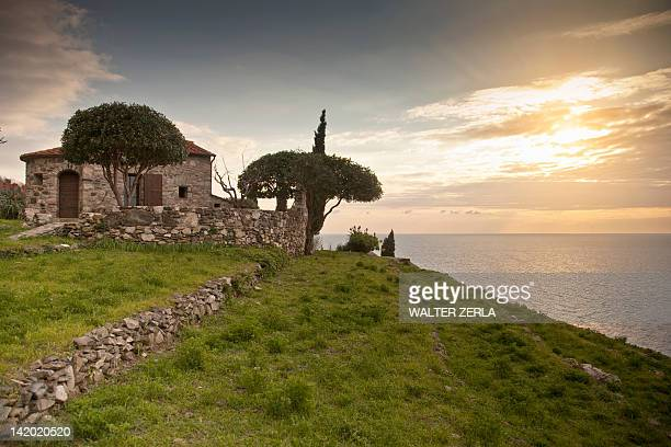stone house overlooking coastline - stone wall foto e immagini stock
