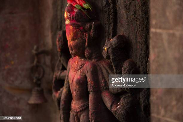 stone idol (devi?) with red kumkum smeared on it and red flowers on the head in the hanuman ghat area of bhaktapur in the kathmandu valley, nepal. - shiva lingam stock pictures, royalty-free photos & images
