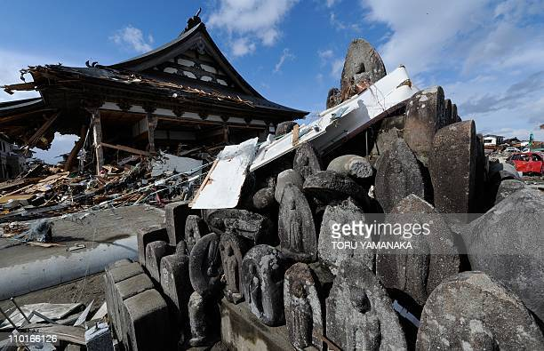 Stone images of Buddha stand in front of a temple damaged by the March 11 tsunami and earthquake in Natori in Miyagi Prefecture on March 16 2011...