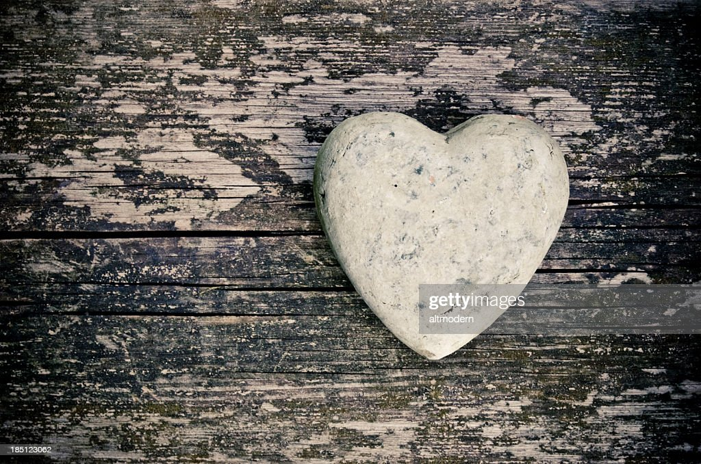 A stone in the shape of a heart on a wooden surface : Stock Photo
