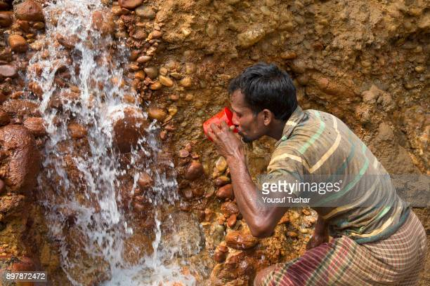 A stone laborer drinking water at Jaflong Stone Quarry field The crystal clear water of the Piyain River which flows from India through Bangladesh is...