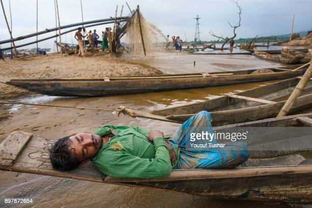 A stone laborer is sleeping on little boat at Jaflong stone quarry fileld The crystal clear water of the Piyain River which flows from India through...