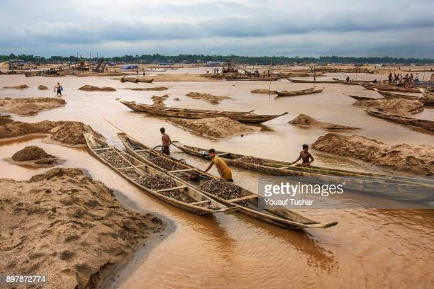 Stone laborers are carrying stones by boat at Jaflong Stone Quarry field The crystal clear water of the Piyain River which flows from India through...