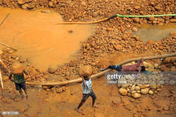 Stone laborers are carrying stones on their heads at Jaflong Stone Quarry field The crystal clear water of the Piyain River which flows from India...