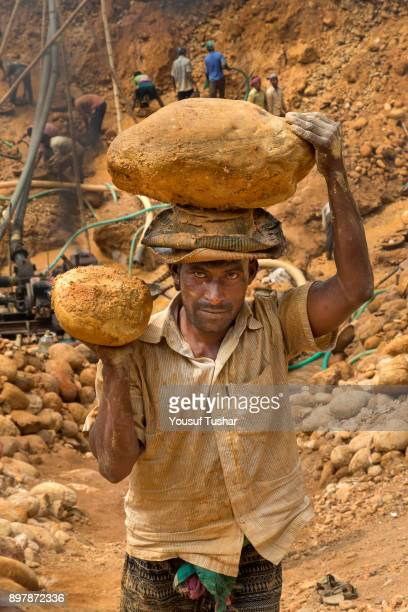 Stone laborers are carrying stones on their over head at Jaflong Stone Quarry field The crystal clear water of the Piyain River which flows from...