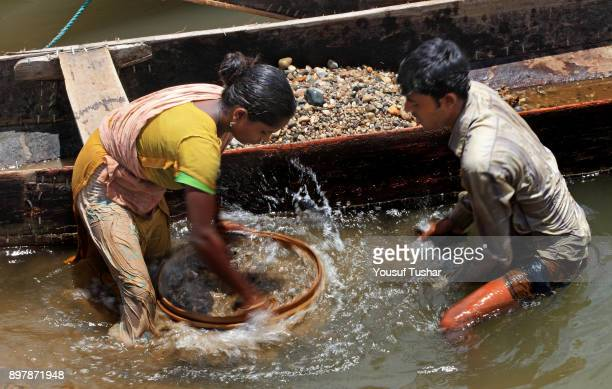 BHOLAGANJ SYLHET BANGLADESH Stone laborers collecting stones at Jaflong Stone Quarry field The crystal clear water of the Piyain River which flows...