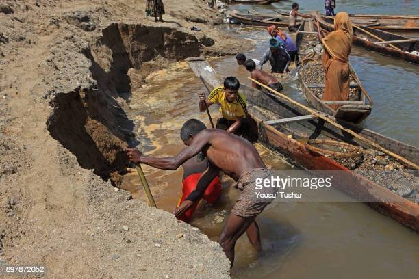Stone laborers digging land at Jaflong Stone Quarry field The crystal clear water of the Piyain River which flows from India through Bangladesh is...