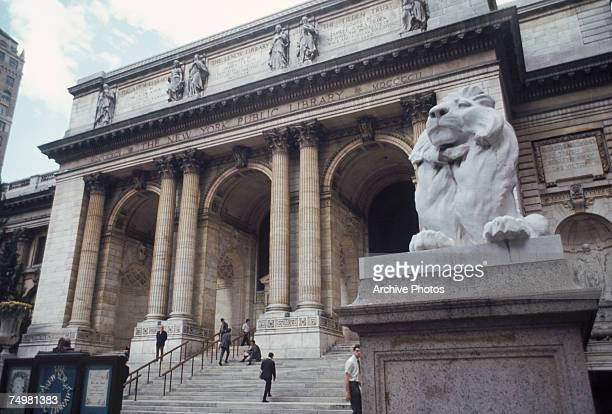 A stone lion guards the New York Public Library in New York City October 1969 The library was formed in 1895 by the amalgamation of the Lenox Library...