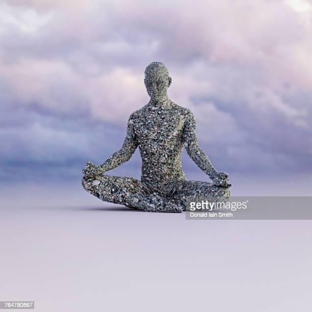 Stone man meditating under clouds