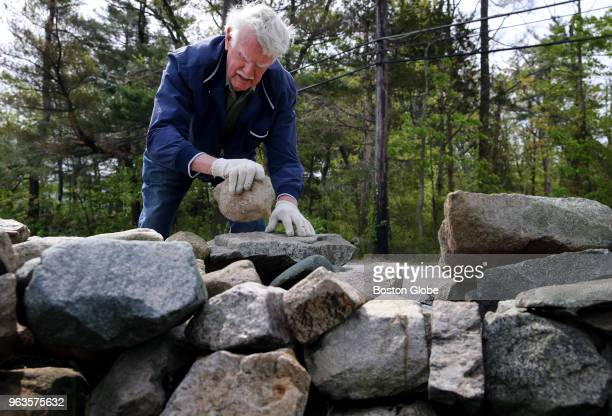 Stone mason Bill Doherty works on repairing a stone wall at Xaverian Brothers High School in Westwood MA on May 18 2018 While many his age spend...