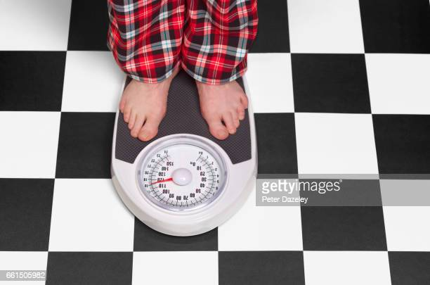 18 stone overweight man on bathroom scales