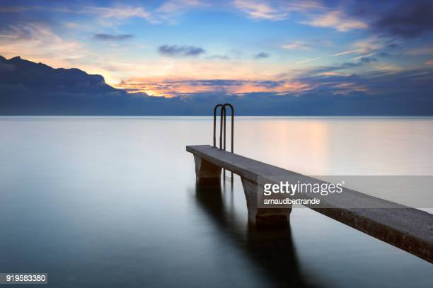 stone pontoon at sunset, lake geneva, haute-savoie, france - jetty stock pictures, royalty-free photos & images