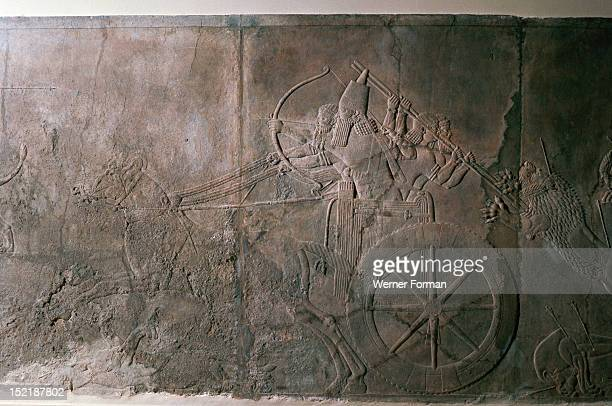Stone relief from the palace of Ashurbanipal The hunt in progress The king fires ahead while his two guards ward off a wounded lion Assyrian Late...