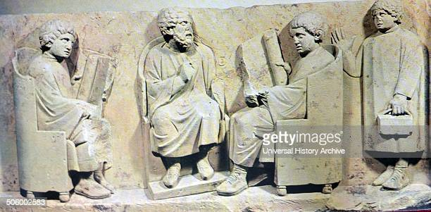 Stone scene depicts a teacher of the Roman School and two students seated during class whilst a third student arrives late Both the teacher and...