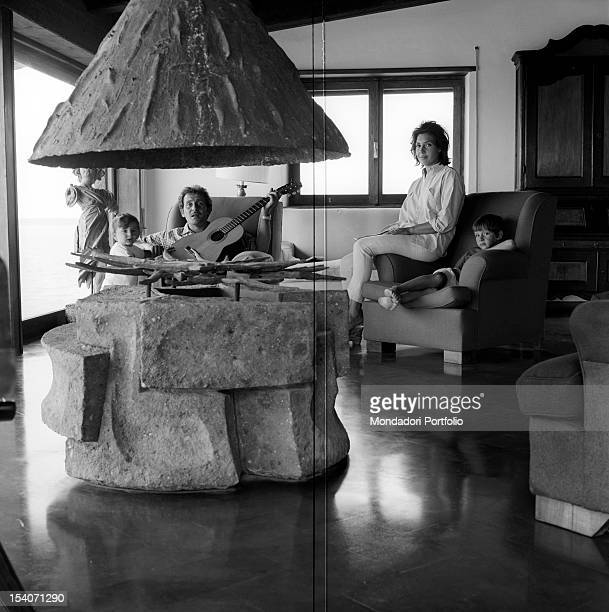 A stone sculpture that has the appearance of a fireplace behind which the little Marcello is next to his father Domenico sitting in a chair guitar in...