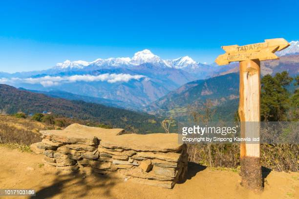 Stone seat and wooden arrow shape direction sign with the beautiful view of Dhaulagiri mountain range in background, Nepal.