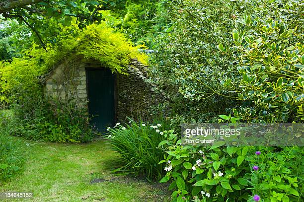 Stone shed in English cottage garden in Swinbrook in The Cotswolds Oxfordshire UK