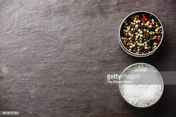 Stone slate background with Sea salt and Multicolored pepper in metal boxes