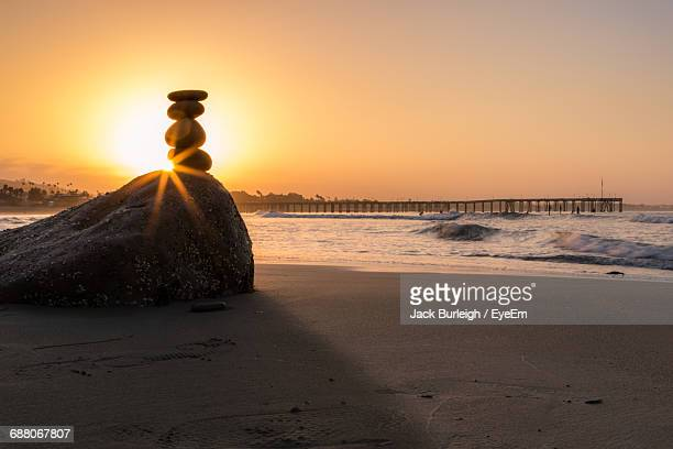 Stone Stack On Beach Against Sky During Sunset