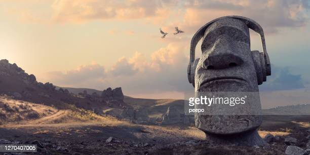stone statue head wearing headphones in remote rocky dawn landscape - mythology stock pictures, royalty-free photos & images