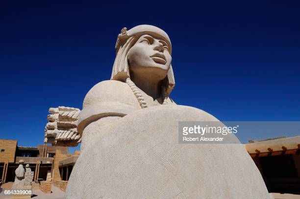 A stone statue stands beside the Sky City Cultural Center and Haak'u Museum at Sky City one of three Native American villages which make up Acoma...